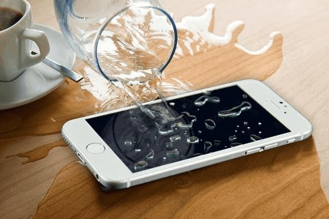 iPhone sobre uma mesa com um copo derramando agua por todo o celular
