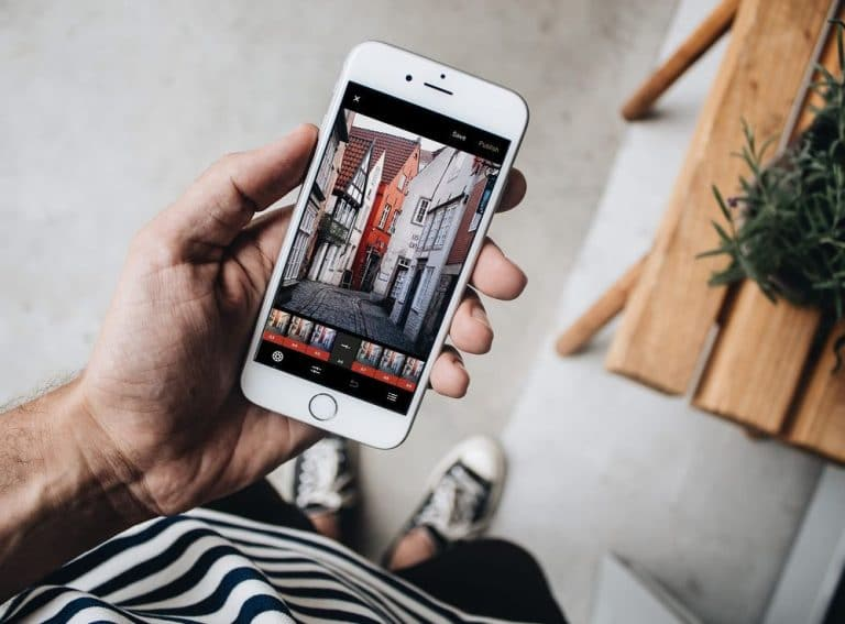 rapaz segurando um iphone com um aplicativo de edicao de imagens na tela