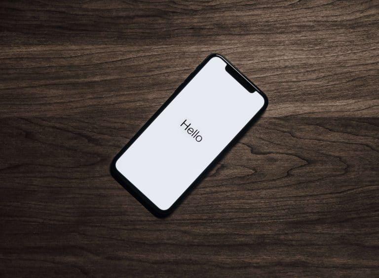 iphone de tela acesa escrito olá sobre uma mesa de madeira