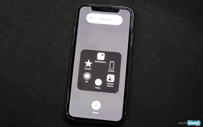 iphone com deslise para desligar e assistive touch abertos em um fundo ou mesa preto.